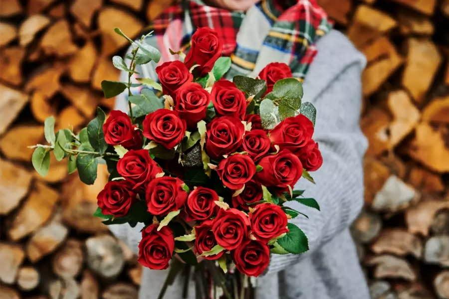 Dame holder en bukett røde roser foran en vedstabel
