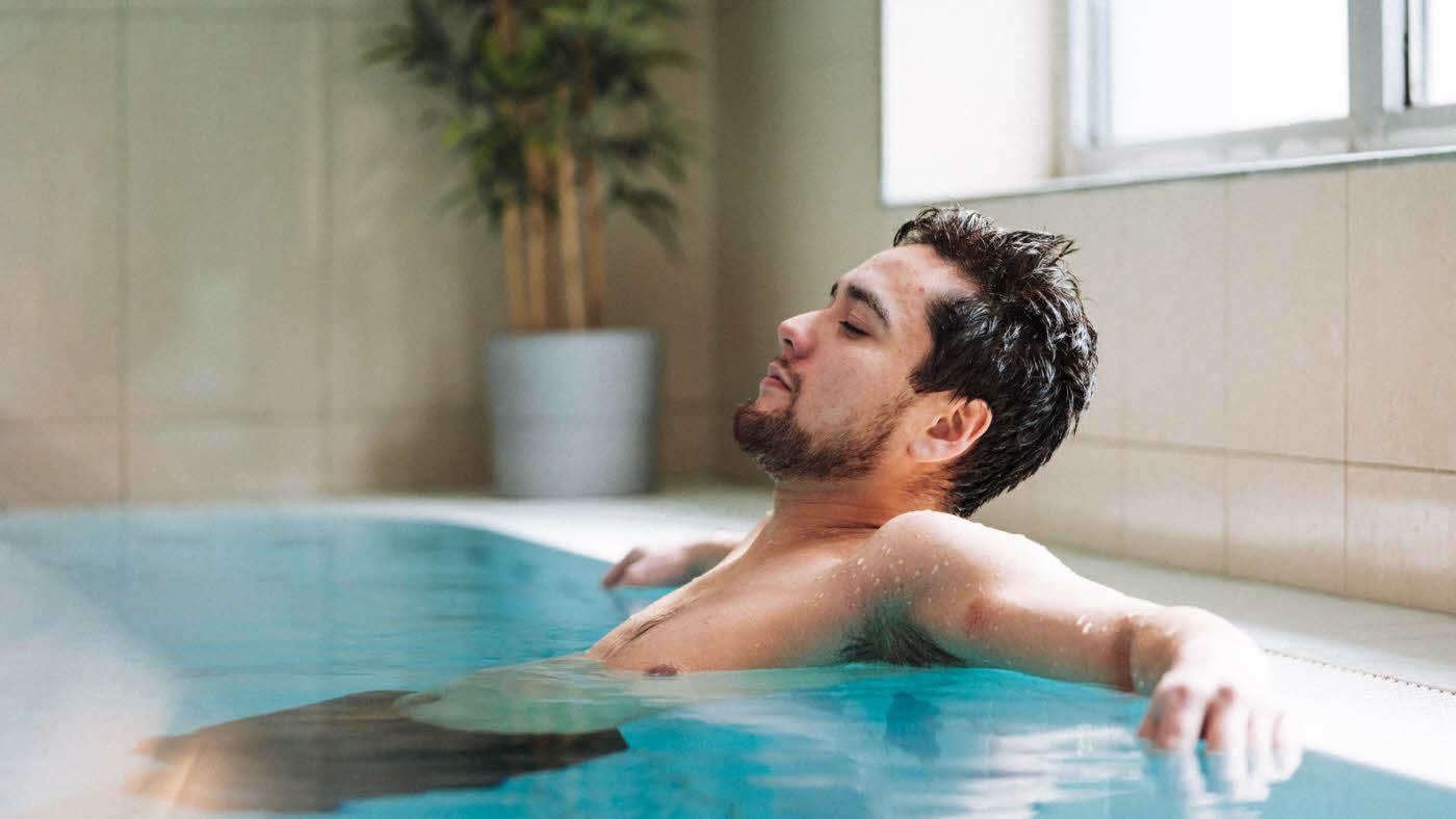 Mann som slapper av i bassenget på Vestkanten Spa