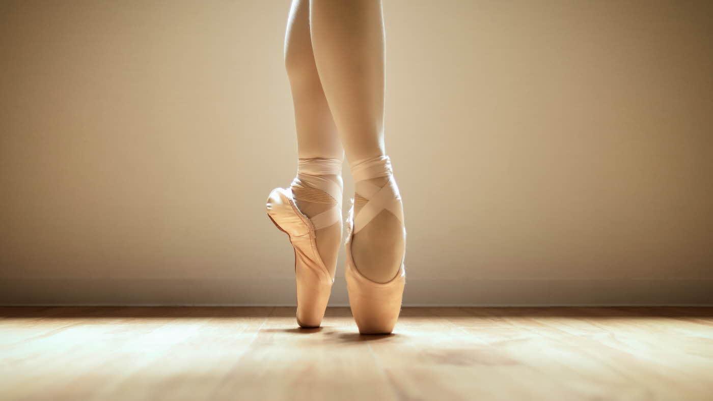 Føttene til ballerina i rosa balletsko