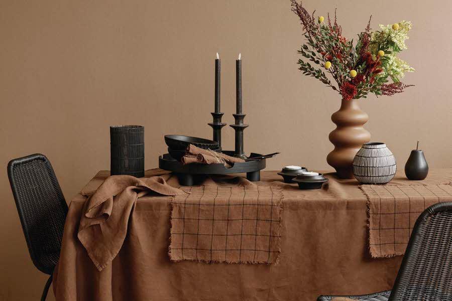 Bord pyntet med blomster, lys og servise