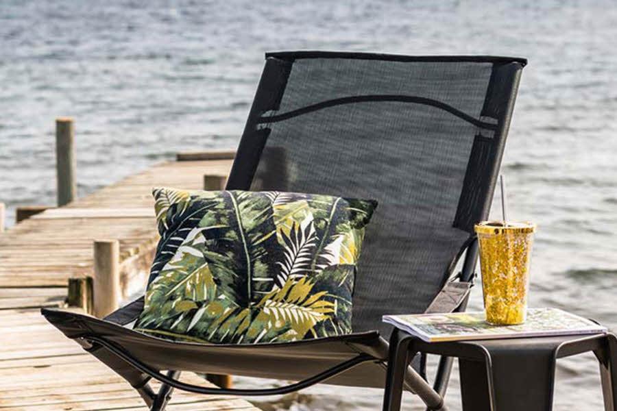 Svart hagestol pyntet med grønn palme pute, med en krakk dekket med en drink ved side av.