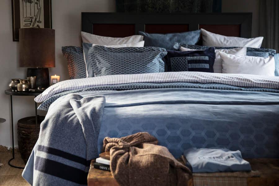 Soverom med oppredd seng i blått sengetøy