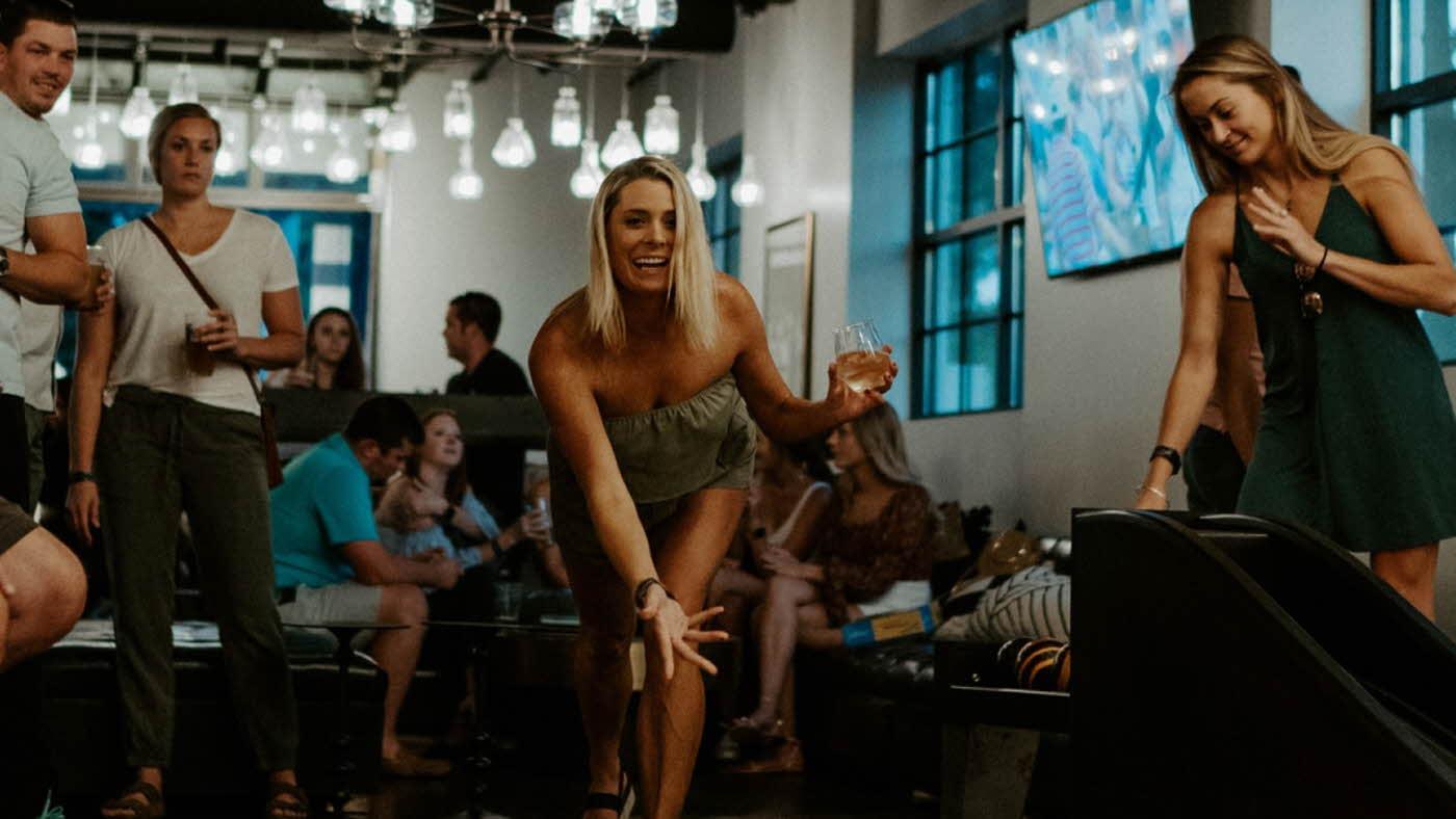 Dame spiller duckpin med folk rundt seg