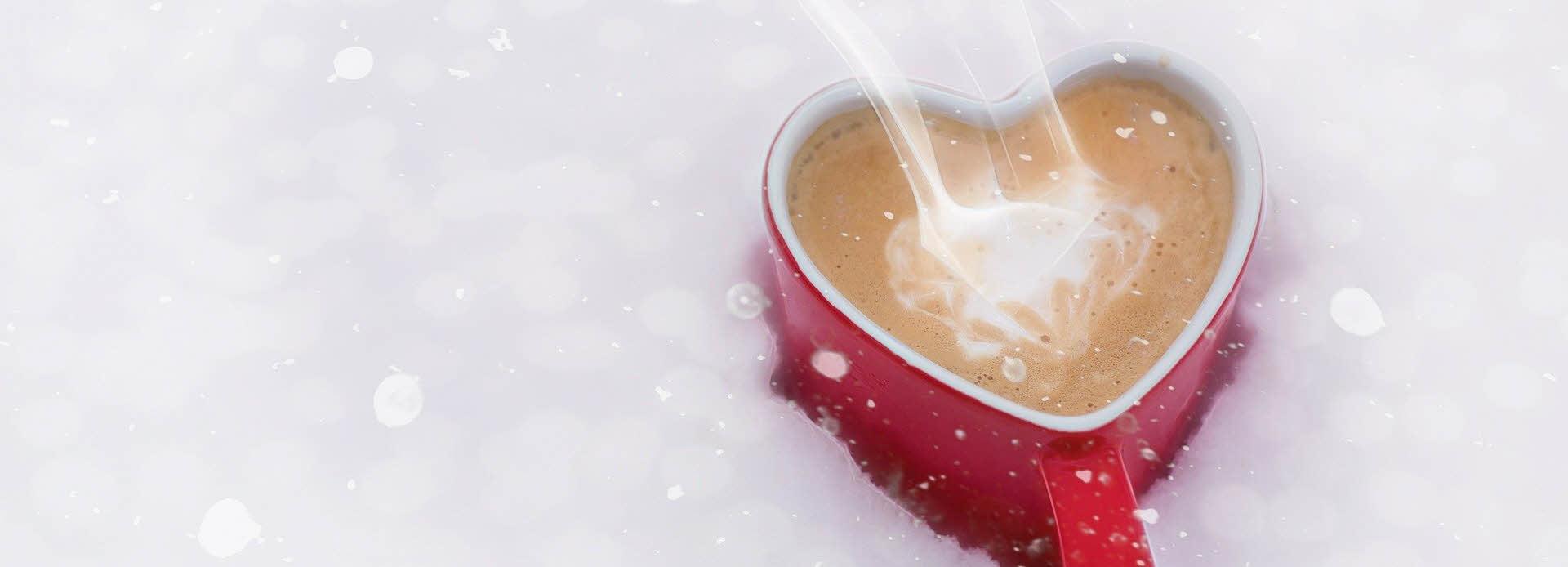 Hjertekopp med kaffe i snøen