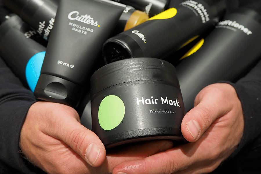 Hender holder mengde hårprodukter