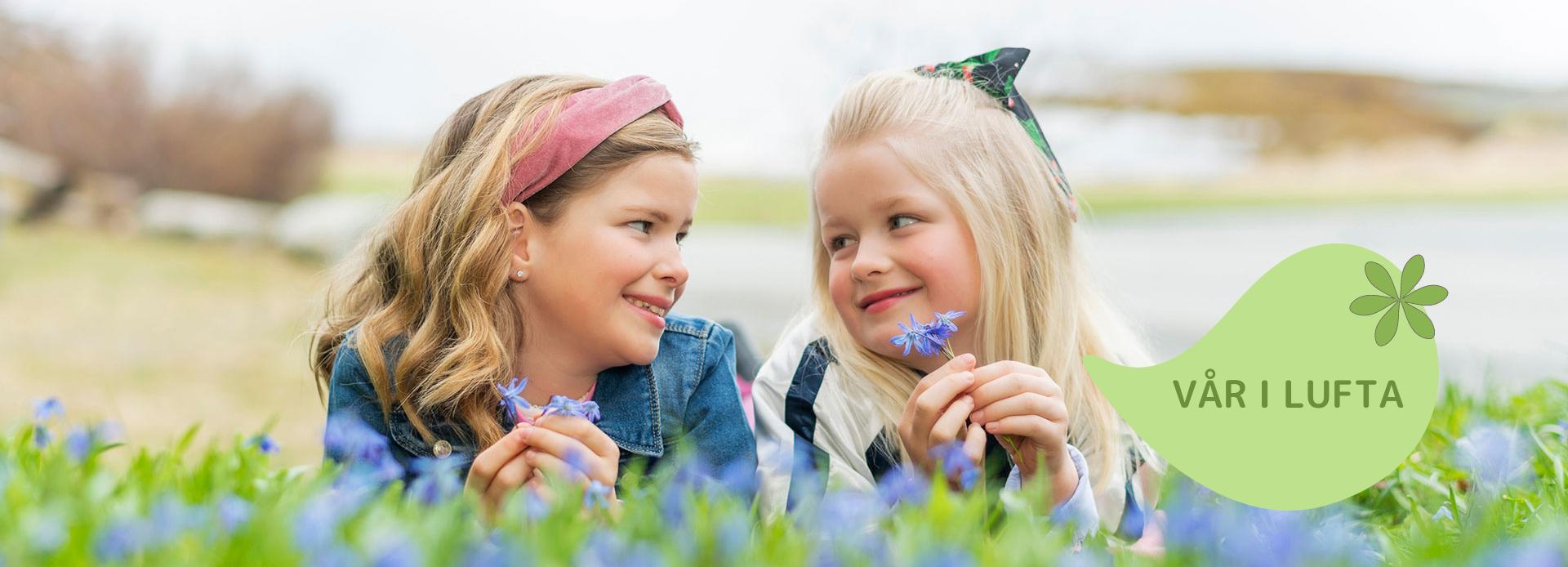 """Jenter liggende i blomstereng med teksten """"vår i lufta"""""""