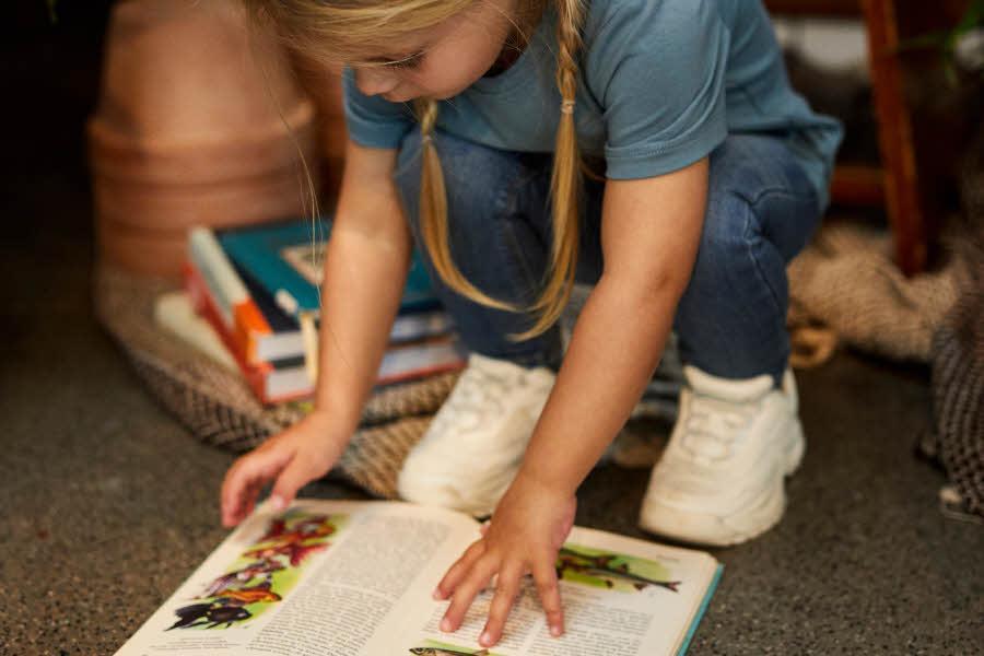 Jente i blå klær som leser en bok
