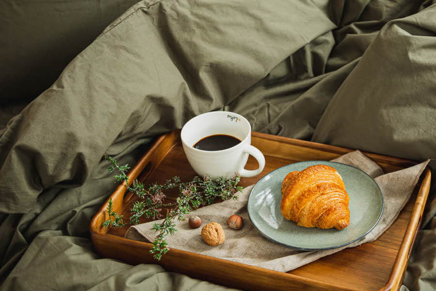 Brett med frokost i en seng