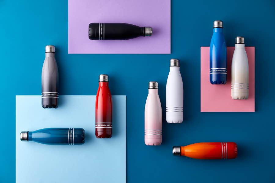 Flasker ligger på fargede flater