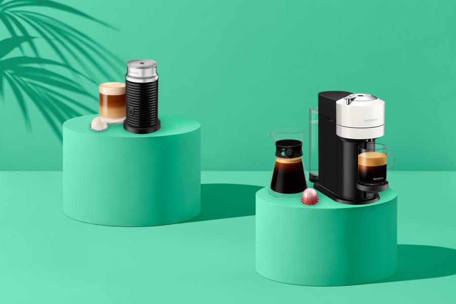 Nespresso maskin og melkeskummer foran grønn bakgrunn