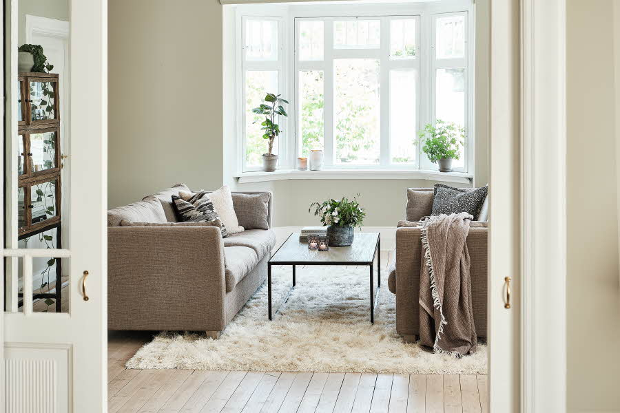 Stue med sofamiljø og bord, lyst og beige farger