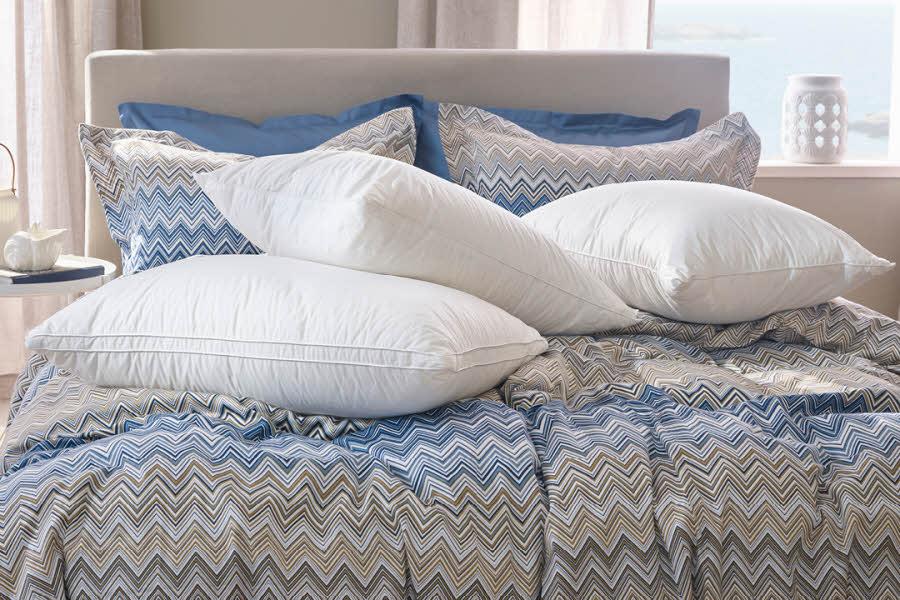 Hvite dunputer ligger på en seng