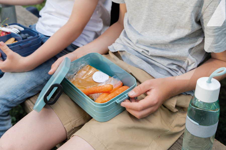 En gutt med matboks og drikkeflaske