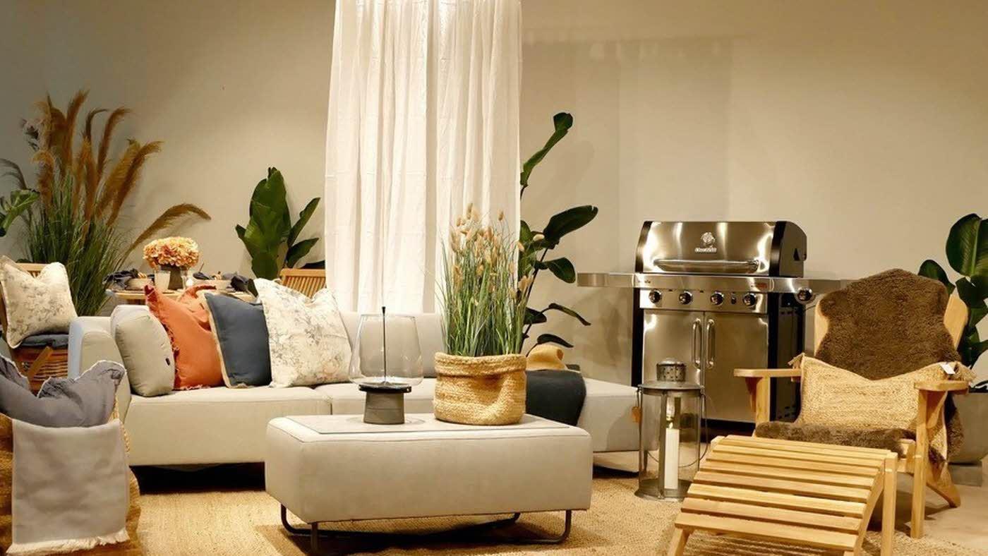 En gruppe utemøbler som er stylet med pledd, lys, blomster og lykter