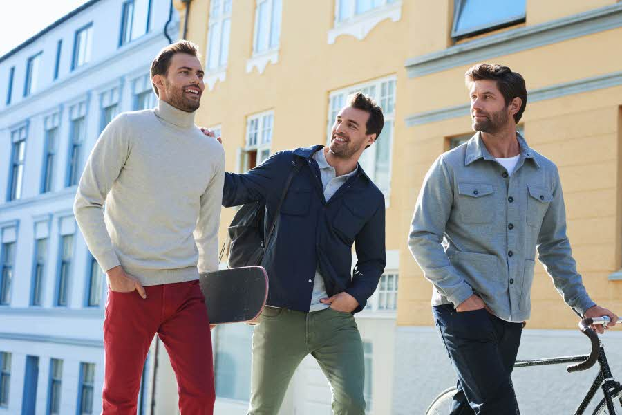 3 menn vandrer nedover en gate
