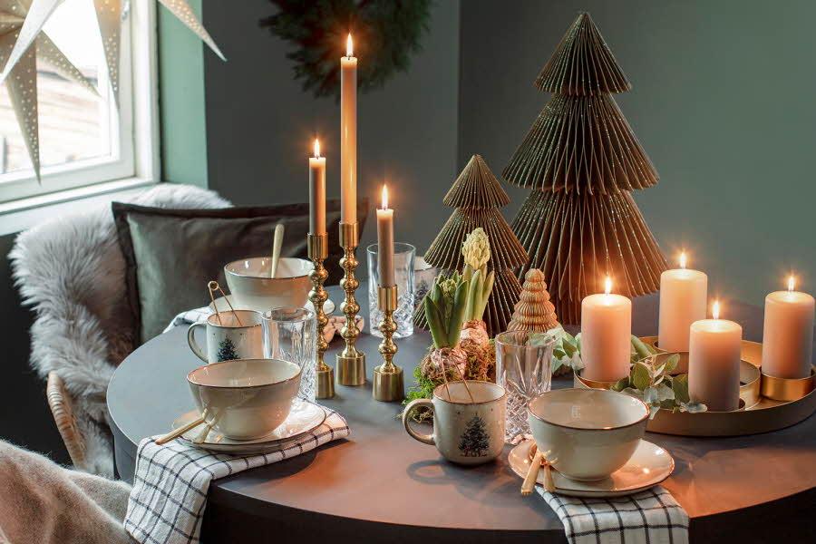 Dekorert bord med kopper, lys og juletre