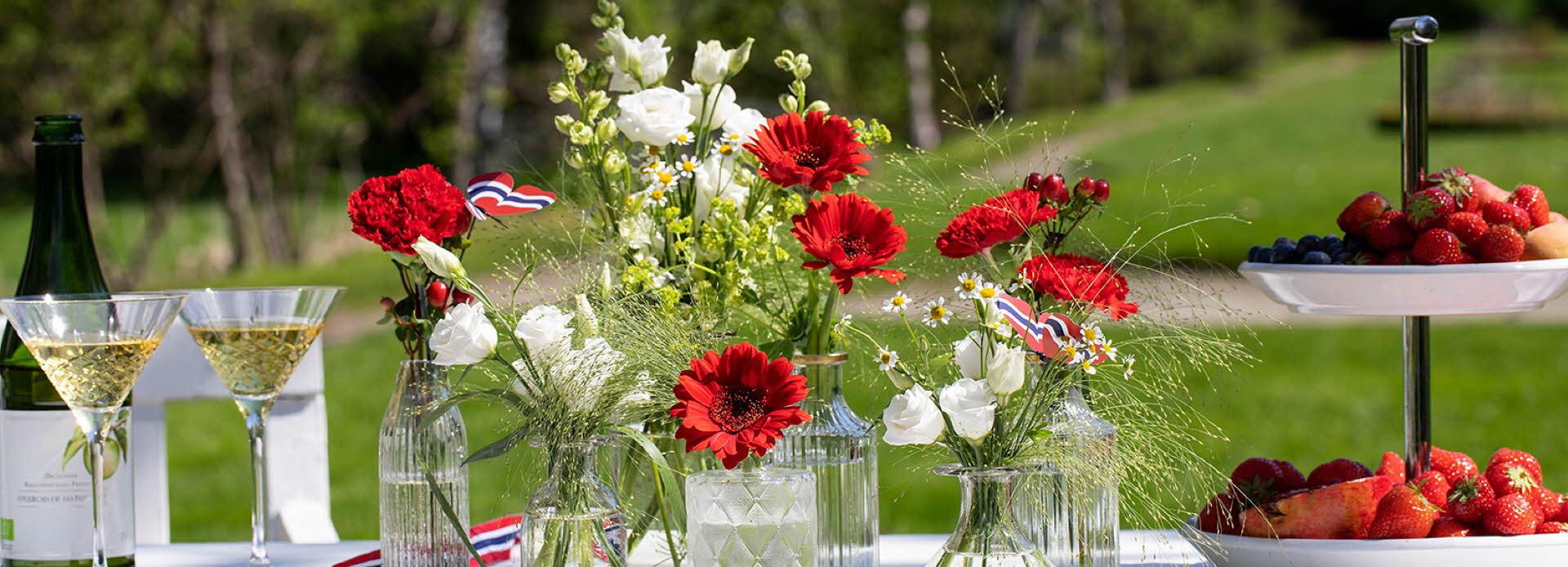 Bord med rød og hvit 17. mai bukett, glass med musserende, etasjefat med jordbær og bånd med norsk flagg.