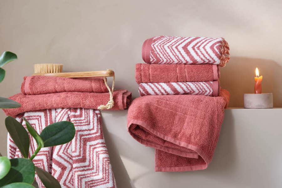 helfargede og mønstrede håndklær ligger på en benk