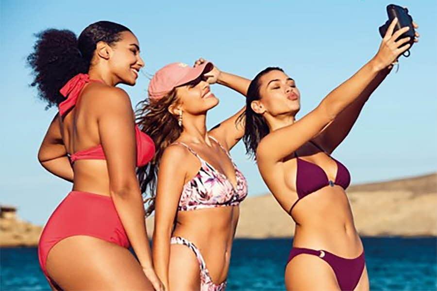 tre kvinner i bikini på stranden som tar selfie