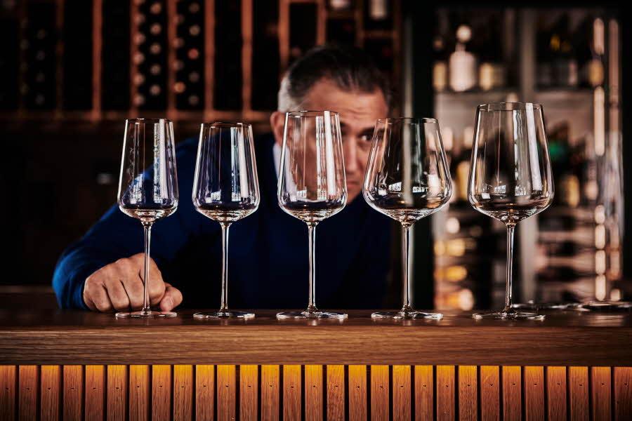 Mann står å ser på vinglass i en bar