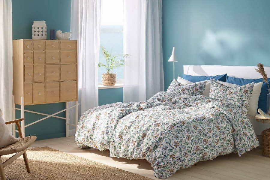 Seng med dyner og puter over seg på et soverom