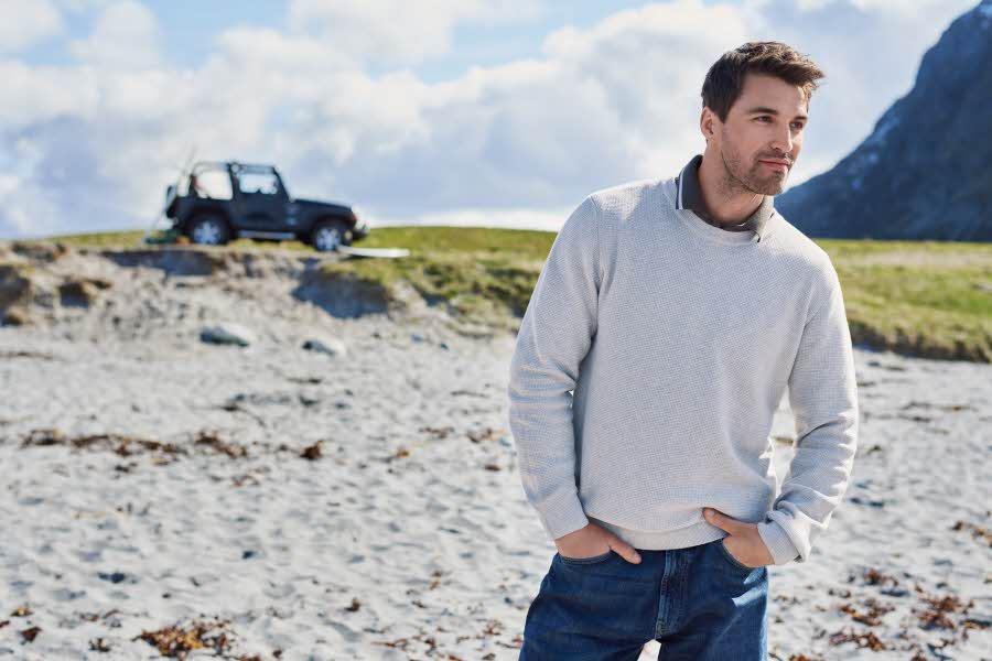 Mann står på en strand