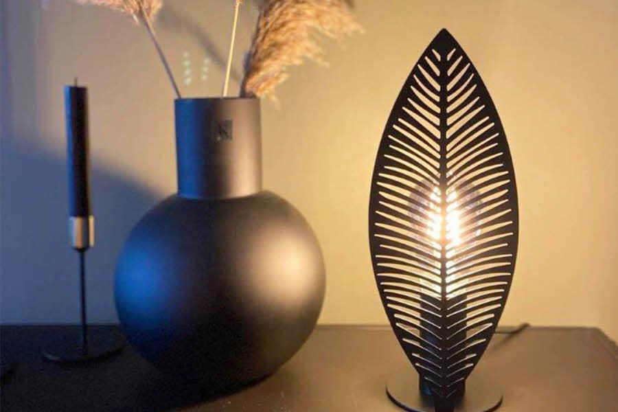 Lampe står på et bord ved siden av plante