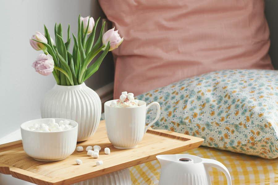 Kopper og blomstervase ved siden av sengen