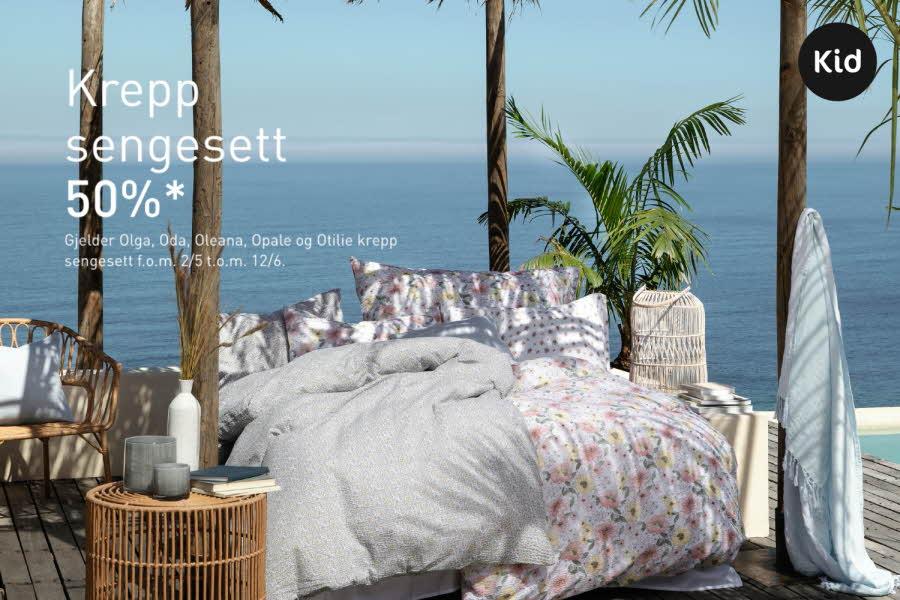 seng på en terrasse ute med dyner og puter, hav i bakgrunnen og grønn plante