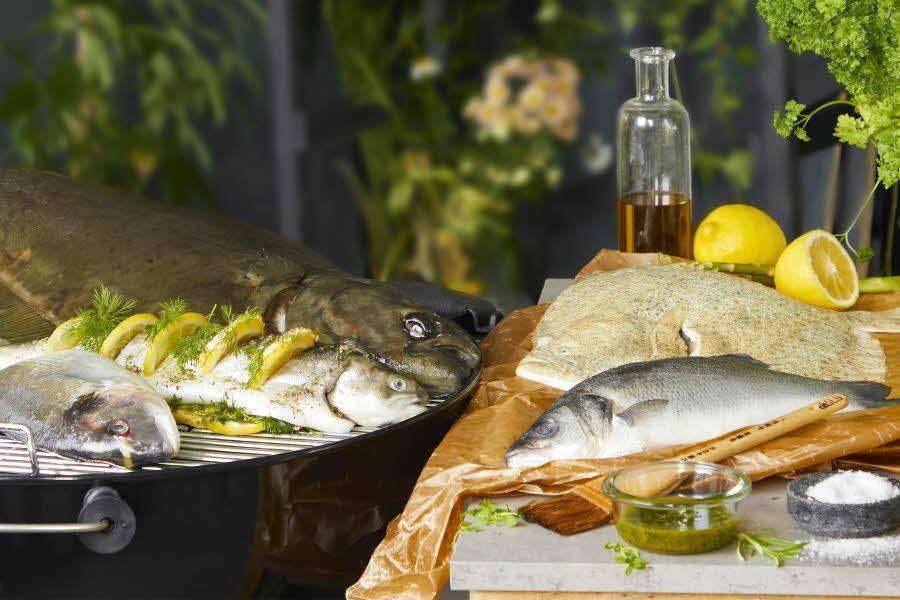 Fisk som ligger på grill ved siden av en fjøl med olje, sitron og salt