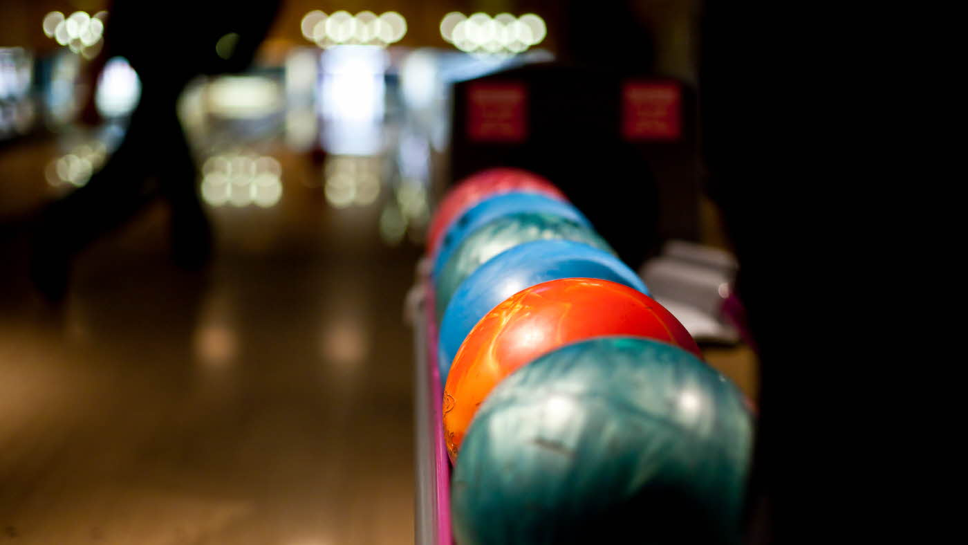 Bowlingkuler på rekke i grønn, oransje, blå og rosa