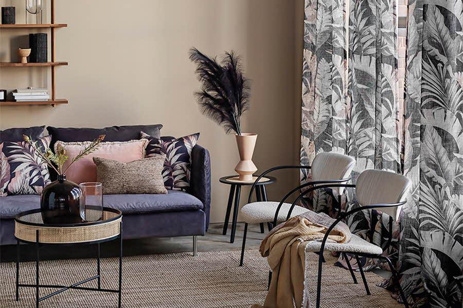Møblert stue med puter, planter og gardiner foran vindu