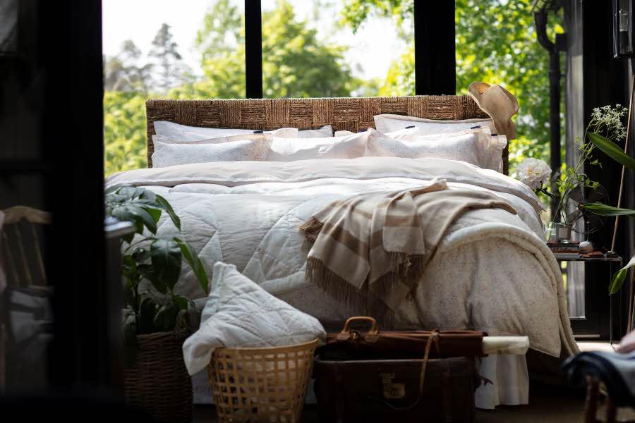 Seng med sengetøy og tepper, ved vindu