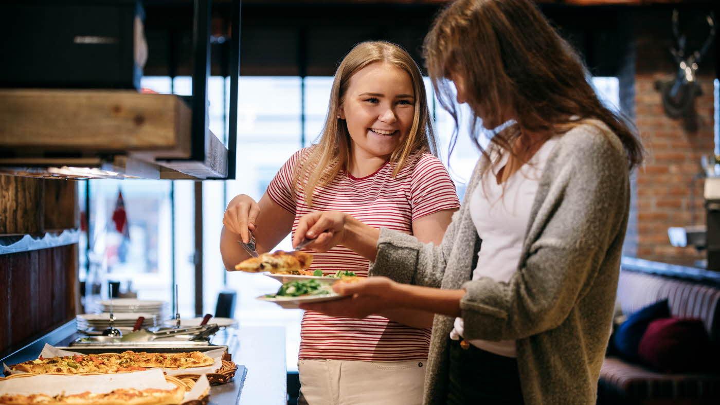 Smilende jente og dame forsyner seg fra pizzabuffet