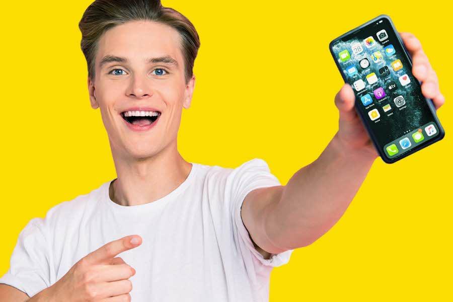 Ung smilende mann i hvit tskjorte som holder en mobiltelefon i hånden