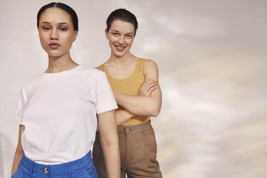 To damer i tank topper foran vegg