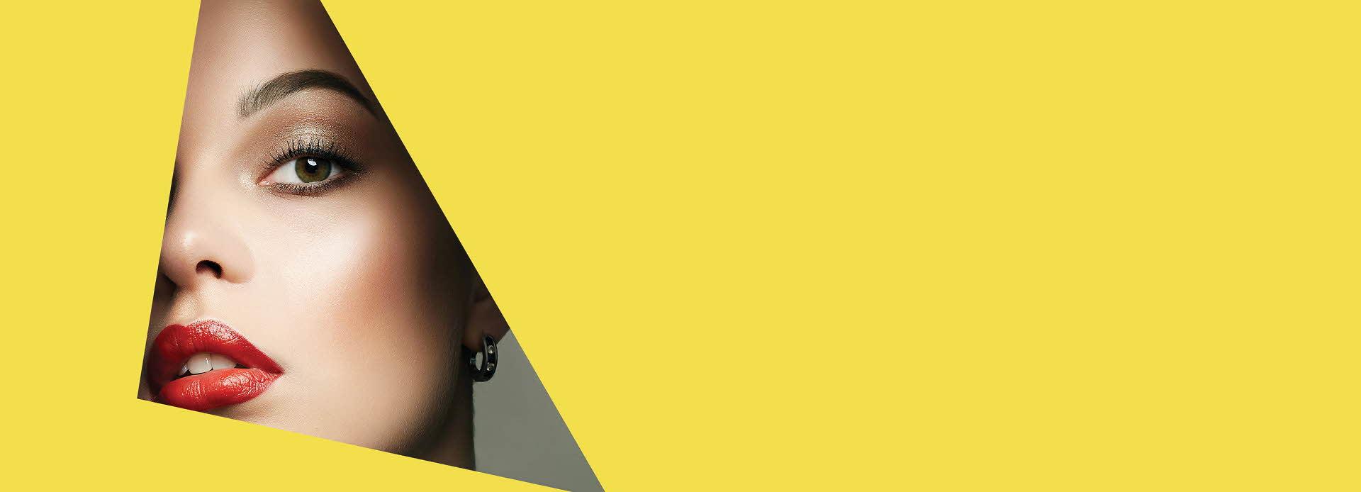 Dameansikt med gul bakgrunn