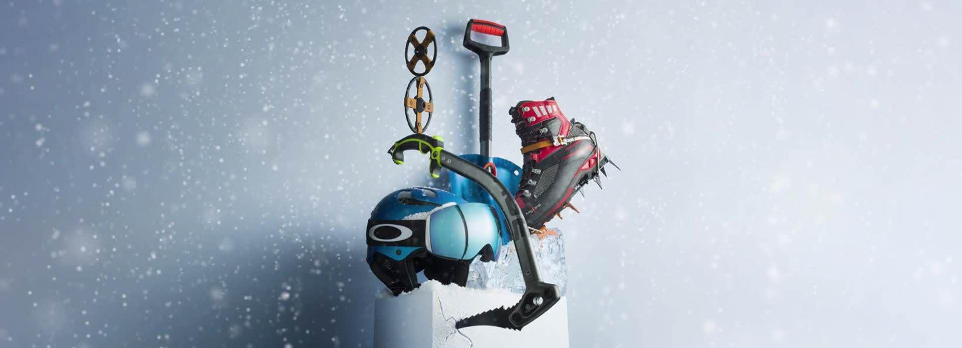 Blåaktig boks med en slålomhjel, slalåmbriller og en ishakke + en vintersko oppå.