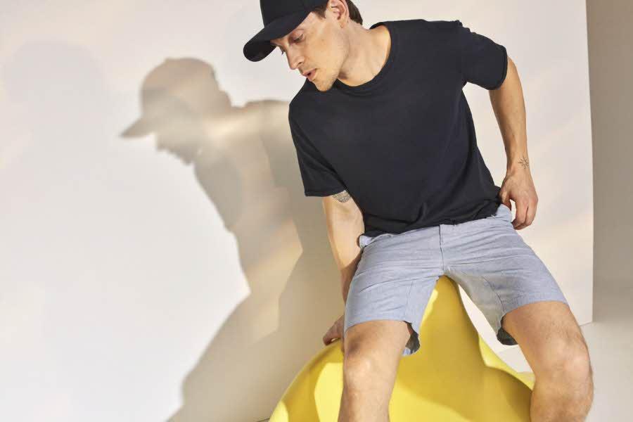 Mann i t-skjorte og shorts poserer
