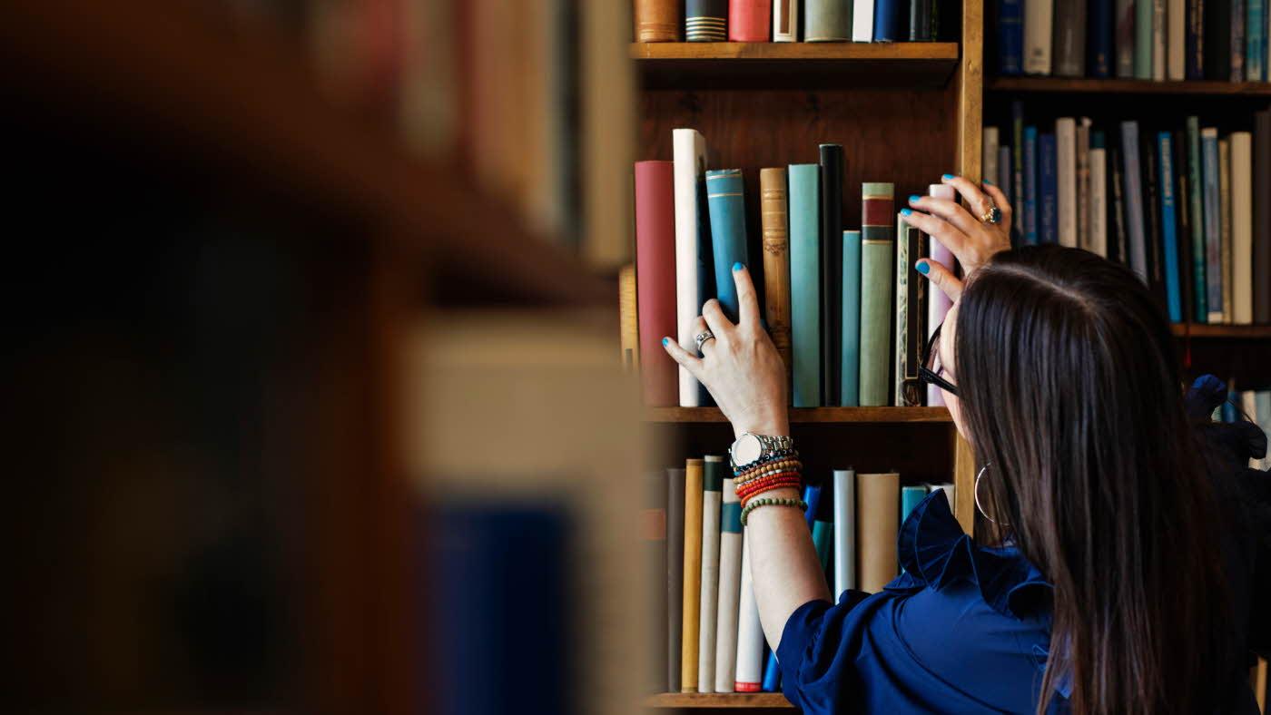 Dame leter etter bok i bokhylle
