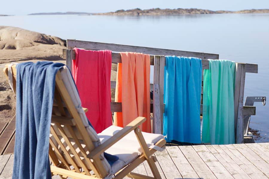 Strandhåndklær i ulike farger hengende over strandstol og rekkverk