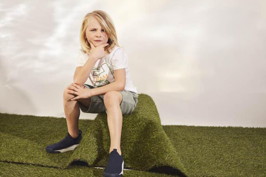 Gutt i shorts og t-skjorte sitter på en kul av gress