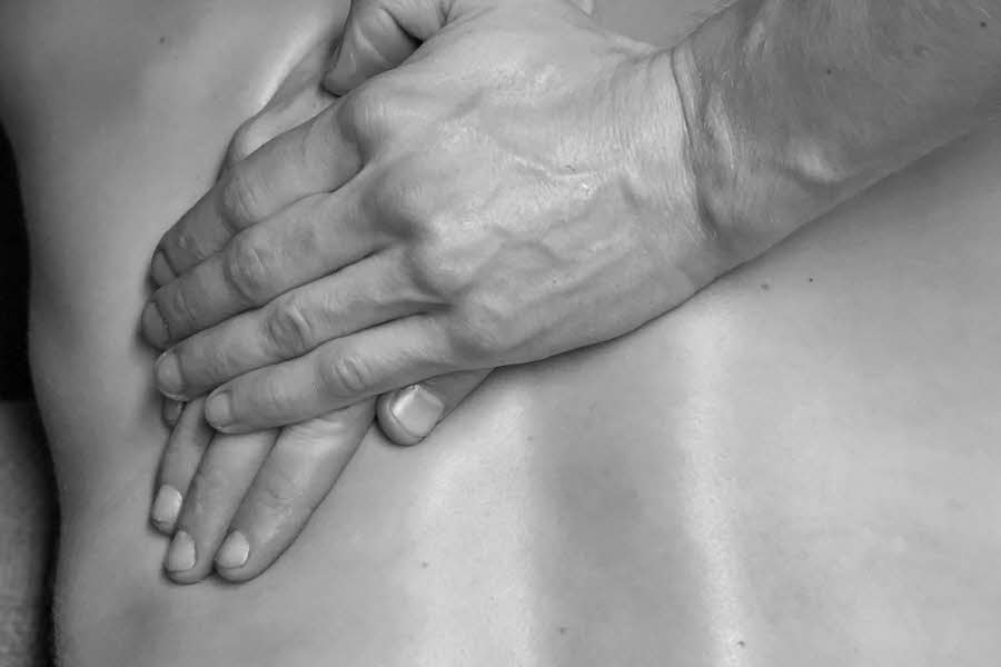 to hender som masserer en rygg
