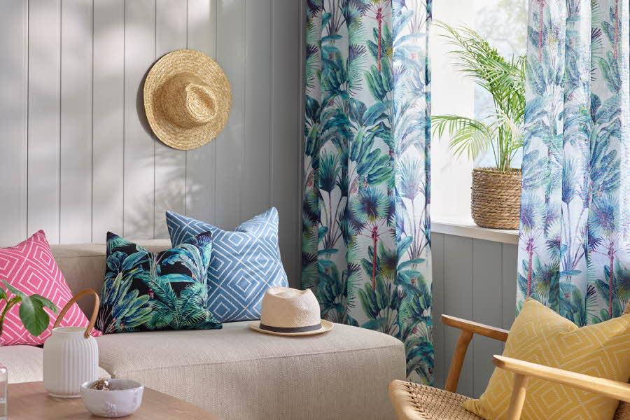 Møblert stue med puter, gardiner og planter