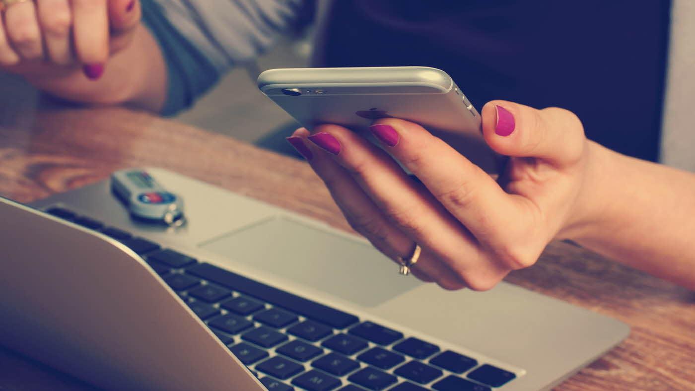 hånd som holder mobil foran dataskjermen