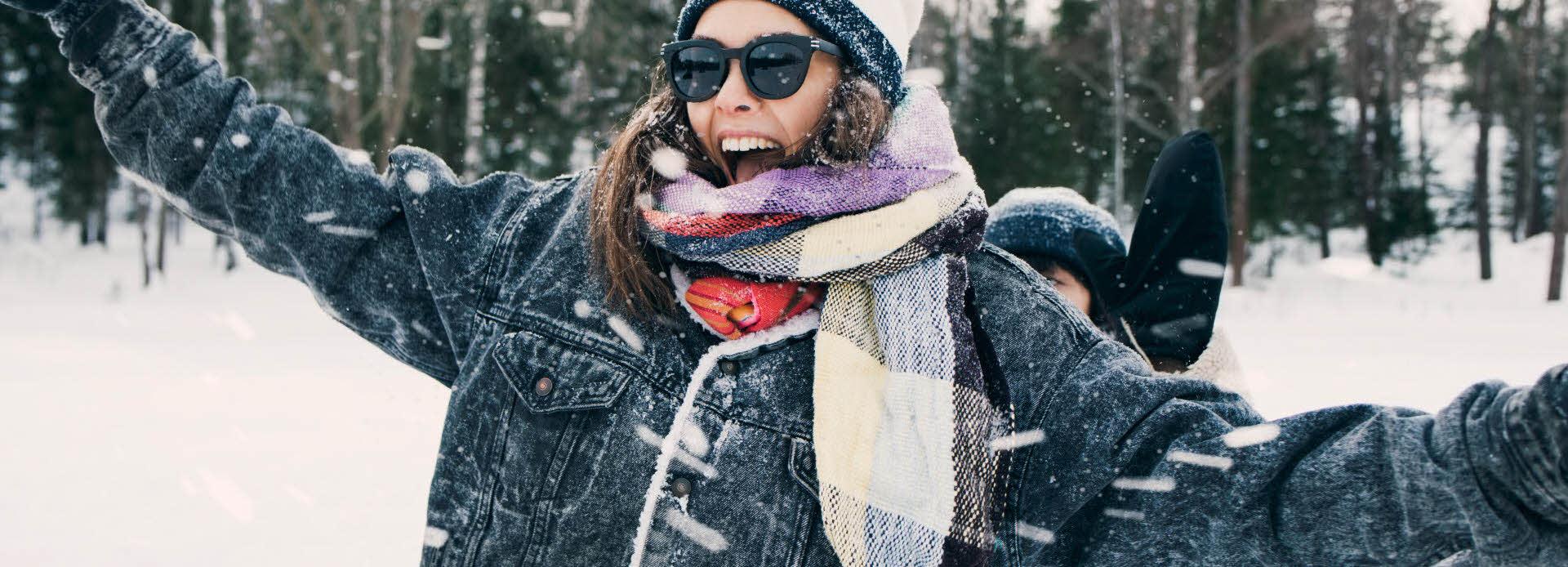 dame med vinterklær som danser i snøen