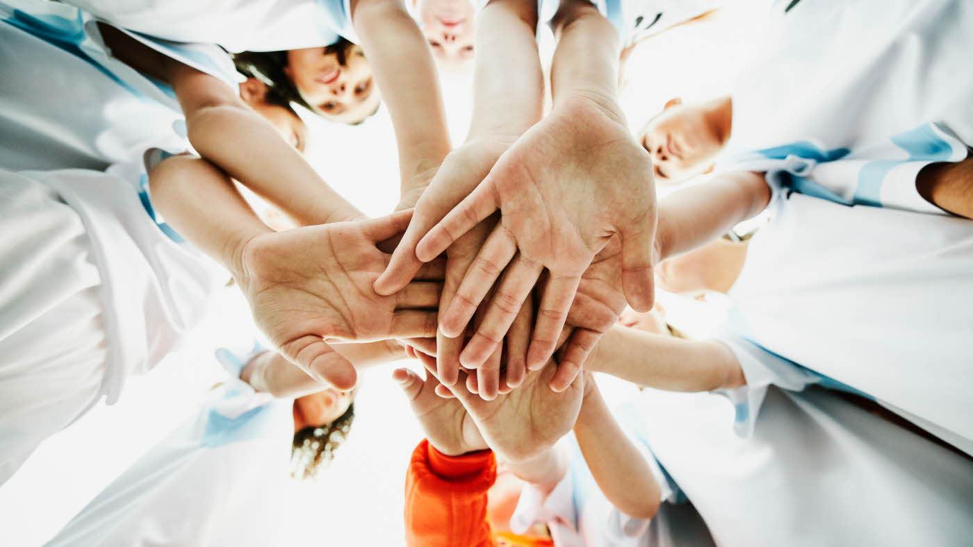 Hender som holdes over hverandre som er klar til å løfte opp for et heiarop under teambuilding
