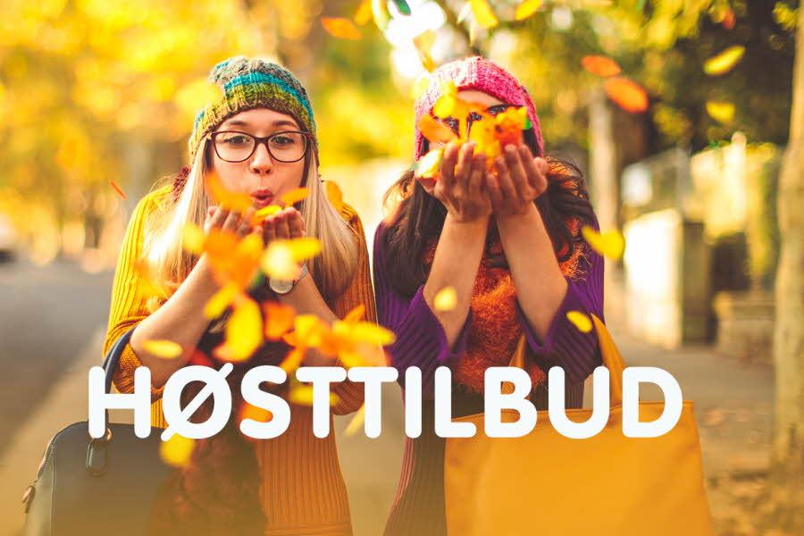 to damer blåser gul og oransje høstløv