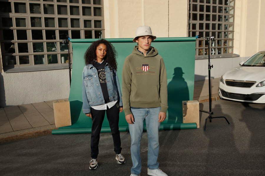 To ungdommer i kule klær står foran en container og en bygning