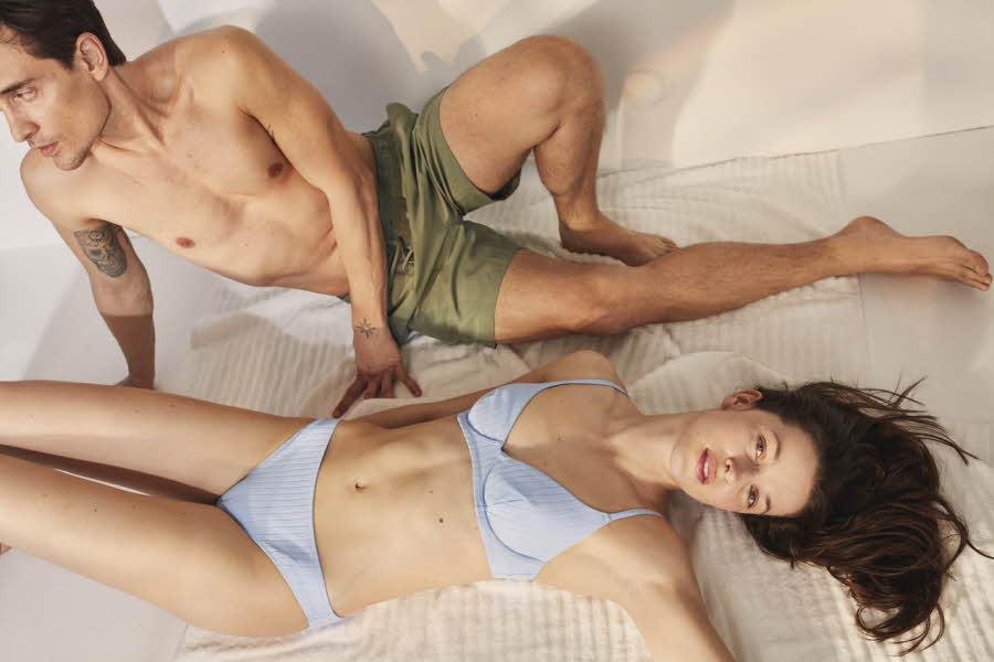 Mann og dame ligger på stranda